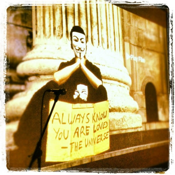 """still image from OCCUPY LOVE: Anonymous masked occupier with sign """"Always remember you are loved - The Universe"""""""